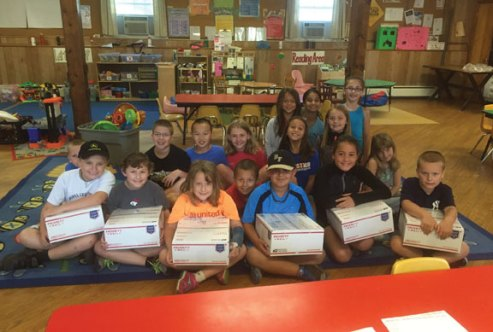 Students from the United Day School in Beacon Falls used money raised during a lemonade stand in July to make care packages for two local soldiers and donated the rest to Beacon Hose Company No. 1. The students raised $400 in total. Pictured, students pose for a picture after making the care packages. –CONTRIBUTED