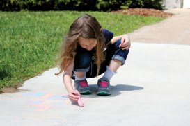 Sofia Sipe, 7, of Prospect, draws a house with chalk on a sidewalk at the Prospect Library Aug. 19 during a town-wide picnic to celebrate the library's 130th anniversary. The celebration included games, crafts and light snacks for visitors. –ELIO GUGLIOTTI