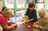 Ah Moi Yip, center, of Cheshire, teaches Prospect residents Trudy Granger, left, and Claire Leo how to fold an origami heart at the Prospect Senior Center Aug. 4. –LUKE MARSHALL