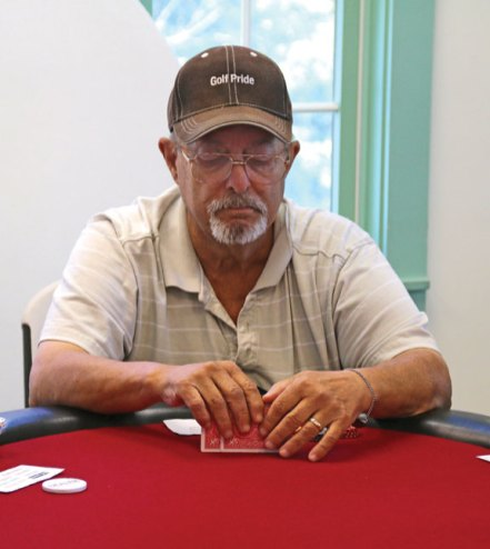 Carmine Midolo, of Prospect, checks his cards during a hand of Texas Hold'em at the Prospect Senior Center Aug. 4. The senior center hosts poker games regularly for seniors. –LUKE MARSHALL