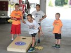 United Day School student Sam Ambrocio, 10, of Beacon Falls, tosses a bean bag during a game of cornhole at the Beacon Falls firehouse Aug. 15 as fellow students, from left, Nick Bousquet, 10, Evan Lin, 11, and Caden Dinsmore, 6, all of Beacon Falls, look on. Beacon Hose Company No. 1 invited the children from the school down for some fun and games and lunch as the summer winds down. –ELIO GUGLIOTTI