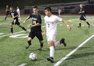 Naugatuck's Thomas Martins (7) pushes the ball up the field as Woodland's Senol Music (18) runs in to defend Sept. 16 in Naugatuck. Naugatuck won the game, 1-0. –ELIO GUGLIOTTI