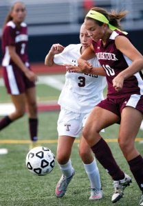 Naugatuck's Kyla Magalhaes, right, and Torrington's Caitlin Perugini battle for the ball Sept. 9 in Torrington. Naugatuck won the game, 4-2. -REPUBLICAN-AMERICAN