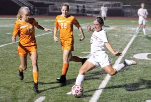 Naugatuck's Kaci Michaud (3) clears the ball past Watertown's Madeline Daigneault (13) and Erin Hughson (22) Oct. 7 in Naugatuck. Watertown won the game, 8-2. –ELIO GUGLIOTTI
