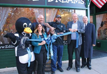 Naugatuck officials marked the opening of Edible Dreams Custom Cakes at 411 North Main St. with a ribbon cutting Oct. 26. Pictured, from left, Edible Dreams Custom Cakes mascot Sweets the Penguin, Naugatuck Chamber of Commerce Director Courtney Ligi, Naugatuck Economic Development Corporation President and CEO Ron Pugliese, Edible Dreams Custom Cakes owner Ed Hughes, Naugatuck Mayor N. Warren 'Pete' Hess and state Rep. David Labriola. –LUKE MARSHALL