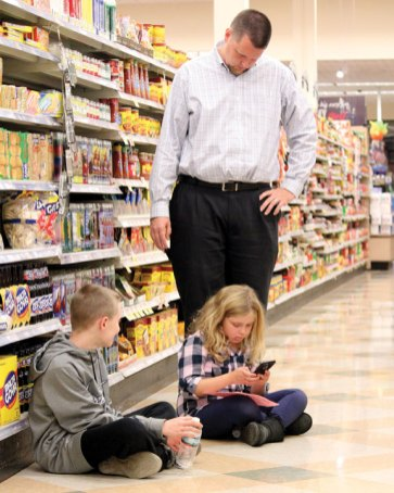 Maple Hill Elementary School third-grader Kayla Gendron works on math problems as her father, Kevin, and brother, Nate, look on during a math night Nov. 14 at Big Y in Naugatuck. Big Y hosted a math night for the school for the second year in a row. About 70 students signed up, those who participated were given worksheets with problems to solve. The problems incorporated activities students could do in the store, like finding certain prices and calculating the average number of steps from the milk to the eggs. –ELIO GUGLIOTTI
