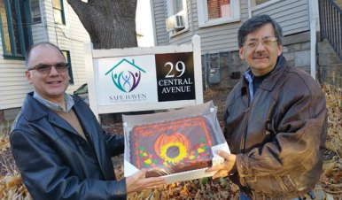 Naugatuck resident Daniel Whitman, right, presents a cake to Safe Haven of Greater Waterbury Executive Director Lee Schlesinger. The cake, which was donated by Costco in Waterbury, was part of a Thanksgiving dinner that Whitman donated to Safe Haven's domestic violence shelter. In recent years, The Manor Inn Restaurant in Southington has prepared the meal. –CONTRIBUTED