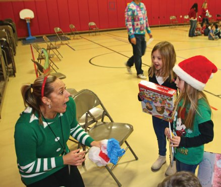 Maple Hill Elementary School kindergartners Mya Evangilista, left, and Paige Kovach hand presents they brought to donate to a toy drive to physical education teacher Angela Loomis Dec. 16 during the school's holiday celebration in Naugatuck. The annual toy drive was run in collaboration with the Naugatuck Fire Department. –LUKE MARSHALL