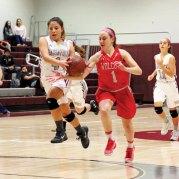 Naugatuck's Michelle Cordova (4) drives to the basket as Wolcott's Alayna Greene (1) swipes at the ball Tuesday at Naugatuck High School. Wolcott won the game, 35-26. –ELIO GUGLIOTTI