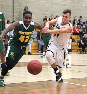 Woodland's Richard Rousseau, right, battles with Holy Cross' Alessandro Ward for a loose ball Monday night in Beacon Falls. Holy Cross won the game, 80-59. –ELIO GUGLIOTTI
