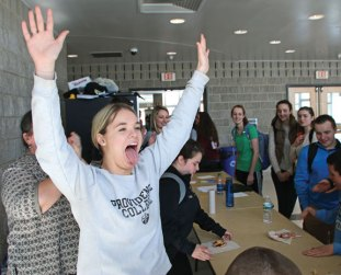 Woodland Regional High School junior Kyla Drewry celebrates after winning a pie eating contest on March 16 at the school in Beacon Falls. The contest was held in celebration of Pi Day, which was March 14. Students also competed in hula hoop and a free hand circle drawing contests. –LUKE MARSHALL