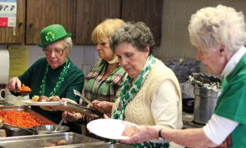From left, volunteers Kathryn Green, Louise Sheedy, Sandra Clark and Carole Mancini prepare dishes for a St. Patrick's Day lunch at the Naugatuck Senior Center on March 17. –ELIO GUGLIOTTI