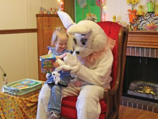Ariebella Paul, 3, of Naugatuck, gives the Easter Bunny a high-five at the Naugatuck Parks and Recreation Department's annual Easter Village April 14. –LUKE MARSHALL