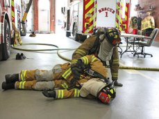 Naugatuck Fire Department probationary firefighters Tim DeBiase, kneeling, and Nick Traycheff take part in a training exercise on June 23 at the firehouse on Maple Street. The exercise was part of Safety Stand Down 2017, a week-long nationwide program. During the exercise, firefighters had to find an injured colleague, hook up a shared oxygen tank and follow a firehose to safety. Firefighters had to wear a cloth over their mask to simulate zero visibility during a fire. Fire Capt. Michael Chatfield said the department does training throughout the year, but last week was the first time it participated in the Safety Stand Down program. –LUKE MARSHALL