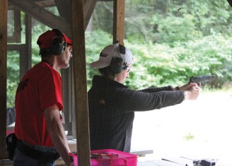 Alison Carroll, of Naugatuck, shoots a 9mm handgun as William Bridges, a volunteer and certified instructor, watches over her during the Women on Target shooting clinic July 29 at the High Rock Shooting Association's shooting range in the Naugatuck State Forest in Naugatuck. About 30 women attended the clinic, which was divided into two sessions. The clinic was sponsored by the High Rock Shooting Association and the National Rifle Association. The clinic is one of several programs hosted annually by the High Rock Shooting Association. It was open to novice and experienced shooters, and is designed to create opportunities, encourage, educate and mentor women's responsible participation in recreational shooting sports. –ELIO GUGLIOTTI