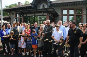 A ribbon is ceremoniously cut Monday to celebrate the opening of The Station, a restaurant at the former train station on Water Street in Naugatuck. –LUKE MARSHALL