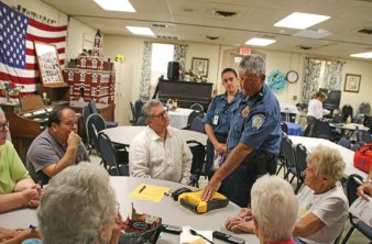 Bob Daley, standing right, and Kayla Gonzalez, standing left, from Naugatuck Ambulance Inc., explain how to use a defibrillator to Naugatuck Senior Center Director Harvey Frydman, center, and six senior center volunteers on Aug. 24 at the senior center. Daley, Gonzalez, Naugatuck Ambulance President Larry Santoro and Naugatuck police Officer Aaron Borys taught the volunteers a number of first aid measures to use in case of an emergency. –LUKE MARSHALL