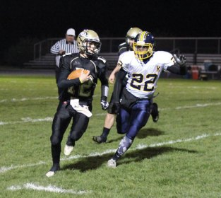 Woodland quarterback Tyler Bulinski (12) runs the ball as Kennedy's Rhakeem Henry (22) gives chase Nov. 9 at Woodland Regional High School in Beacon Falls. Woodland won the game, 49-12. –ELIO GUGLIOTTI