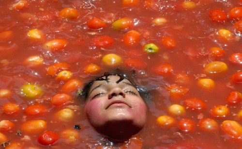 A child rests inside tomato pulp as part of the celebration of Holi in Hyderabad India on February 28 2010