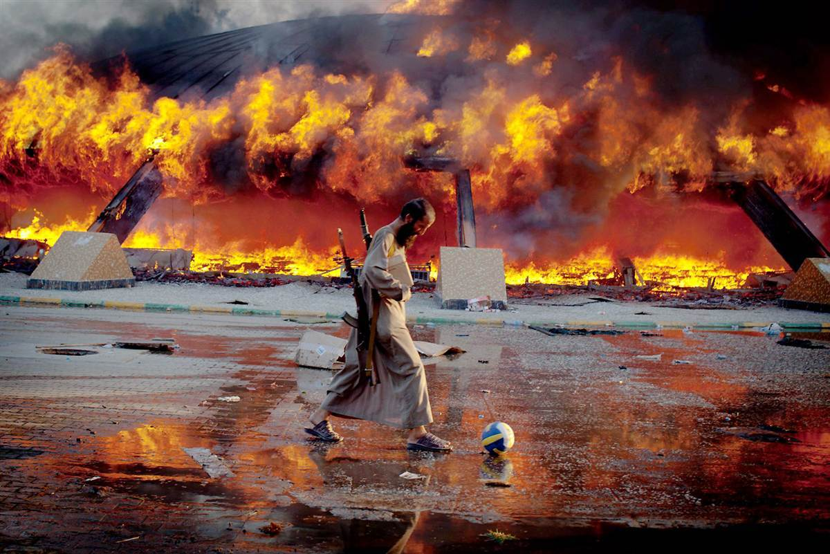 A rebel fighter kicks a soccer ball near Moammar Gadhafi's Bab al-Aziziya compound as it is engulfed in flames in Tripoli Libya Aug 23 Libyan rebels captured the palace after days of fighting for control of Tripoli 1200?