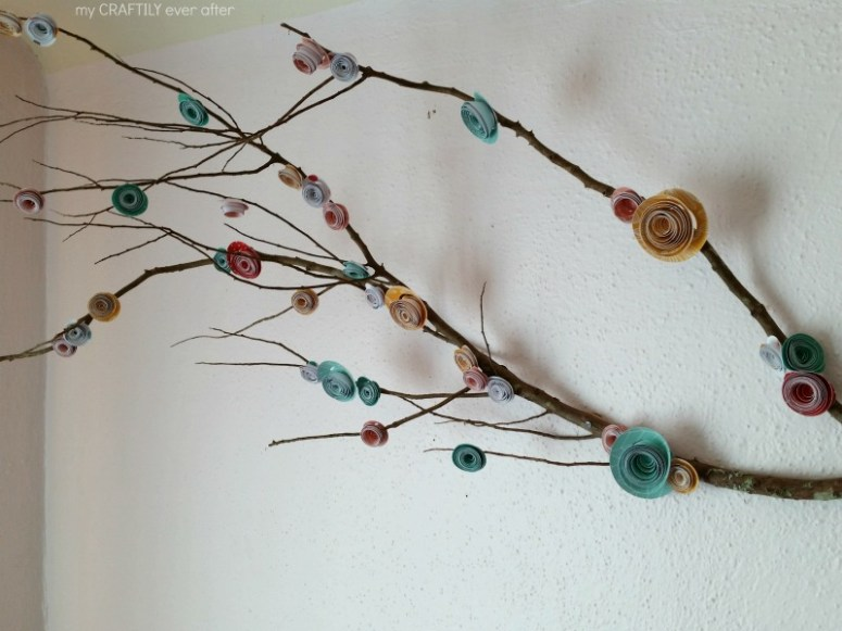 diy rolled paper flowers on a branch