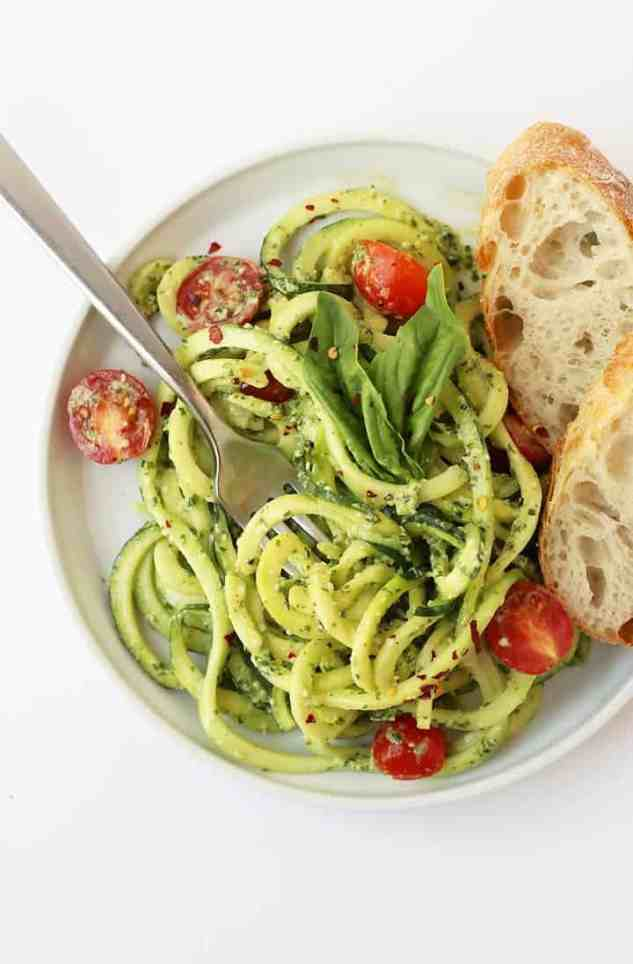 Zucchini Noodles with Pesto on a white plate with bread