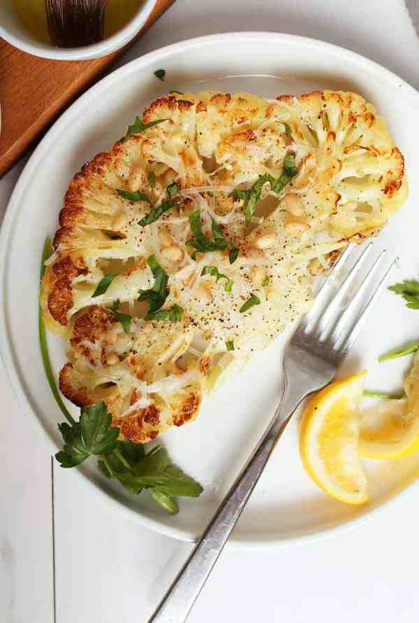 Cauliflower steak with fresh parsley and lemon wedges on a white plate.