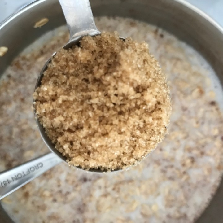 brown sugar in a measuring spoon over a pot of cinnamon and oatmeal porridge