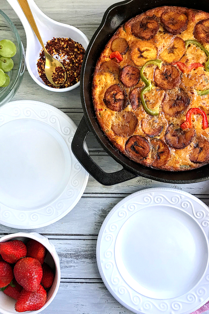 Plantain Frittata ready to be served from a cast iron skillet onto two empty plates with strawberries and grapes on the table