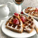 Gingerbread waffles served in a plate topped with raspberries , powdered sugar and a drizzle of syrup