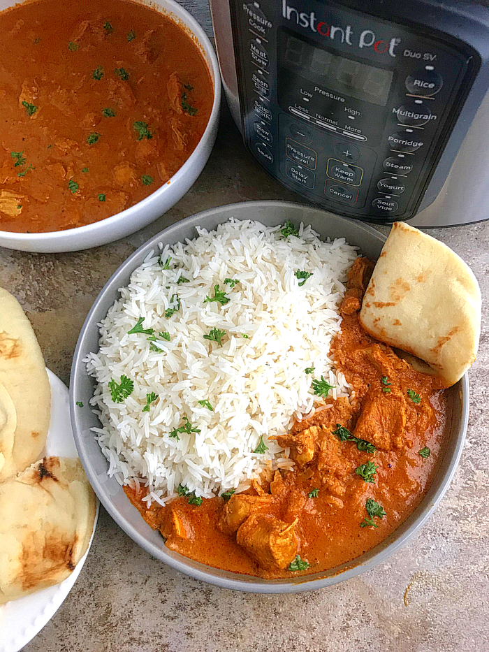Instant pot Chicken tikka masala served with rice and naan. an instant pot in the background