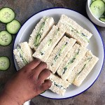 A plate of cucumber sandwiches with a hand over it