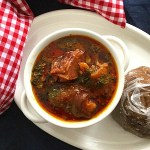 Top view of Nigerian Ogbono Soup win a white plate. with a side of eggplant swallow wrapped in cling film
