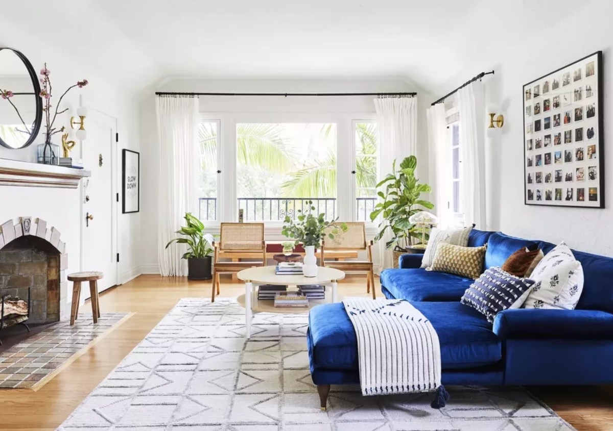 Living room with blue L-shaped couch, two chairs, and white, airy curtains