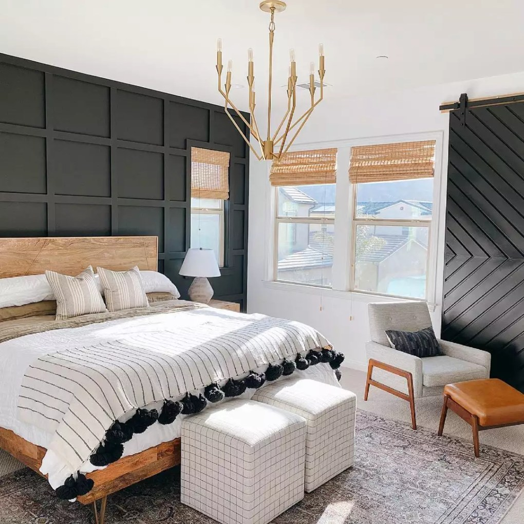 Neutral bedroom with metal chandelier and wooden bedframe.