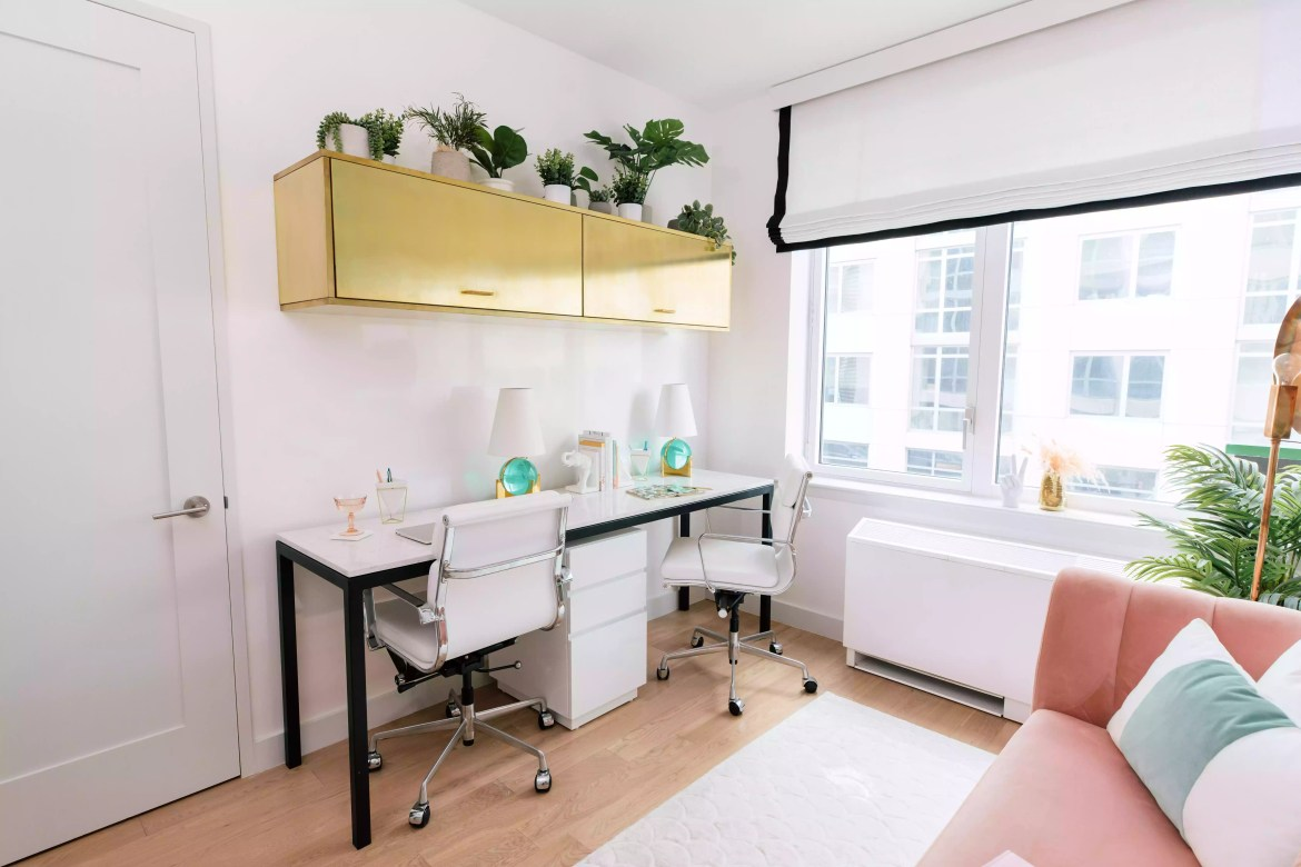 White office desk with gold cabinets above.