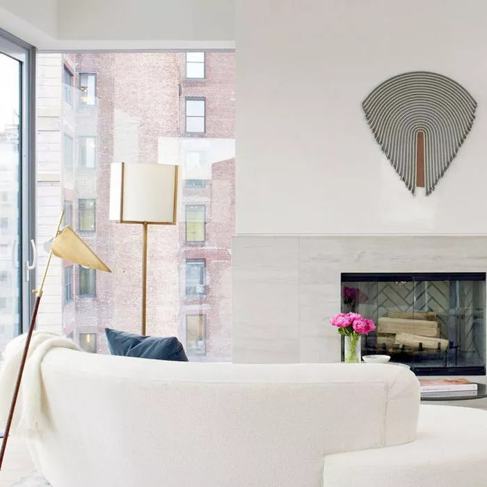 living room with sculptural object hanging above fireplace