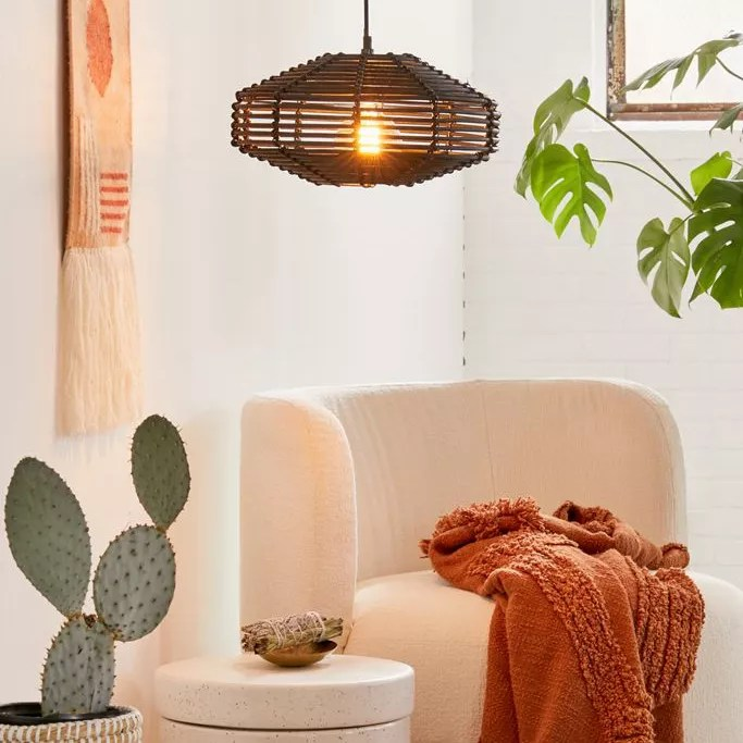 A black rattan chandelier hanging in a decorated interior