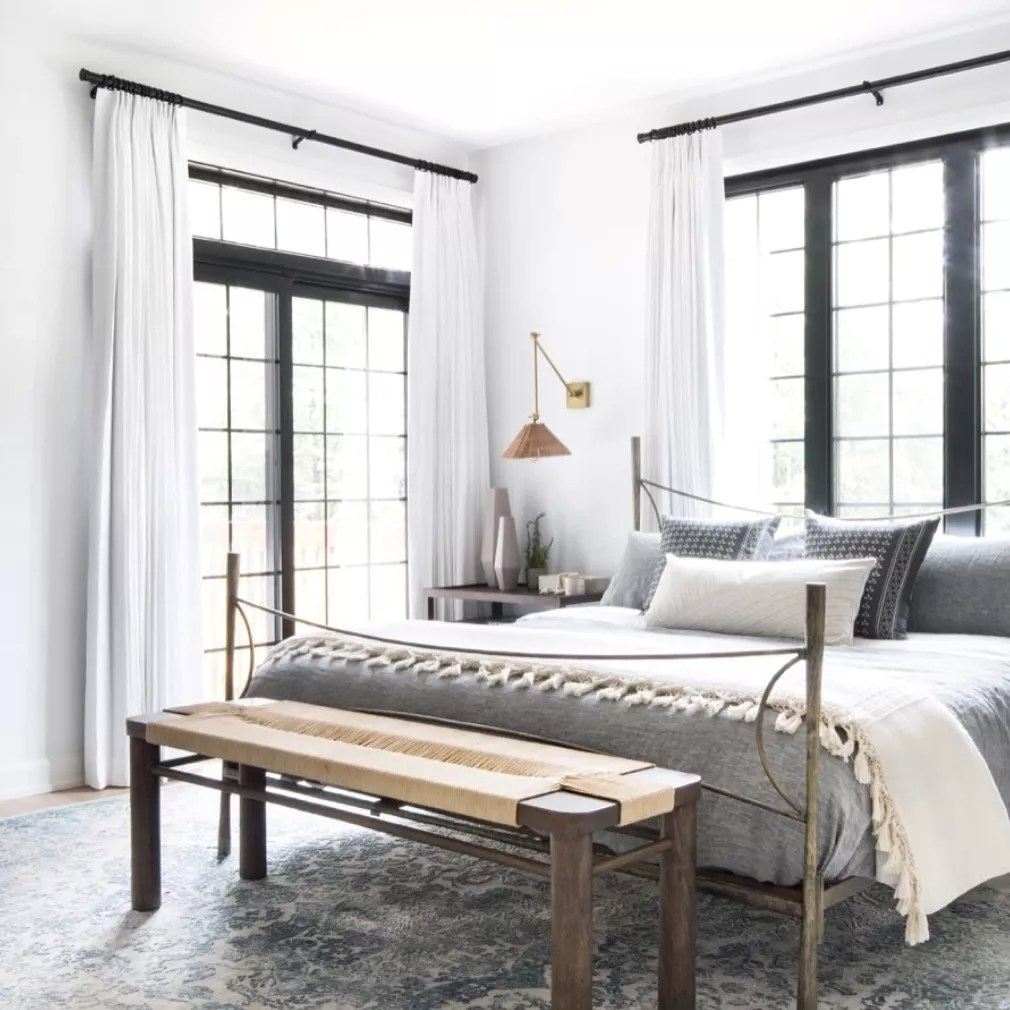 A modern bedroom with a woven sconce