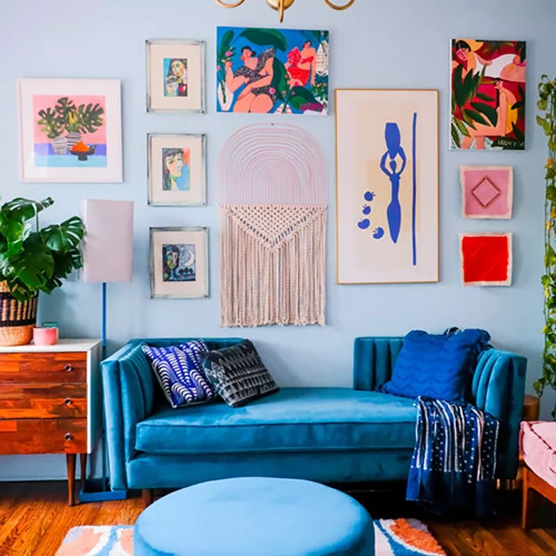 Bright blue sitting room with gallery wall.