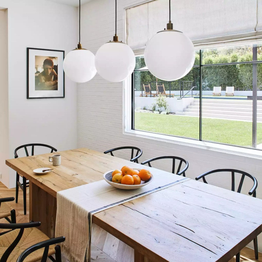 A dining room with a wooden table and a linen table runner that's been turned sideways