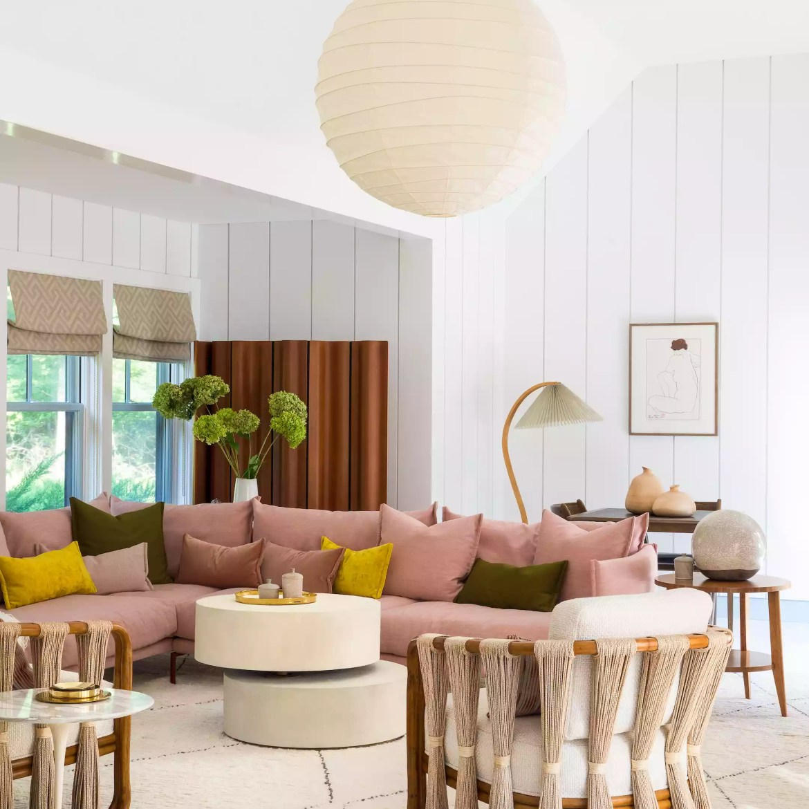 Living room with large lantern chandelier and pink sofa.