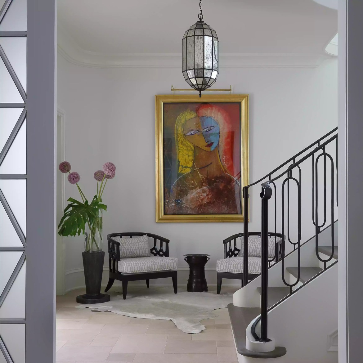 Luxe entryway with chandelier and rug.
