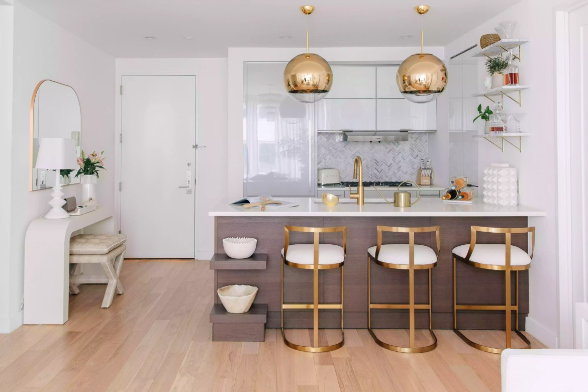 Gold pendant lighting matching barstools at kitchen island.
