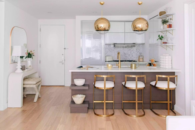Gold pendant lighting matching barstools at kitchen island.