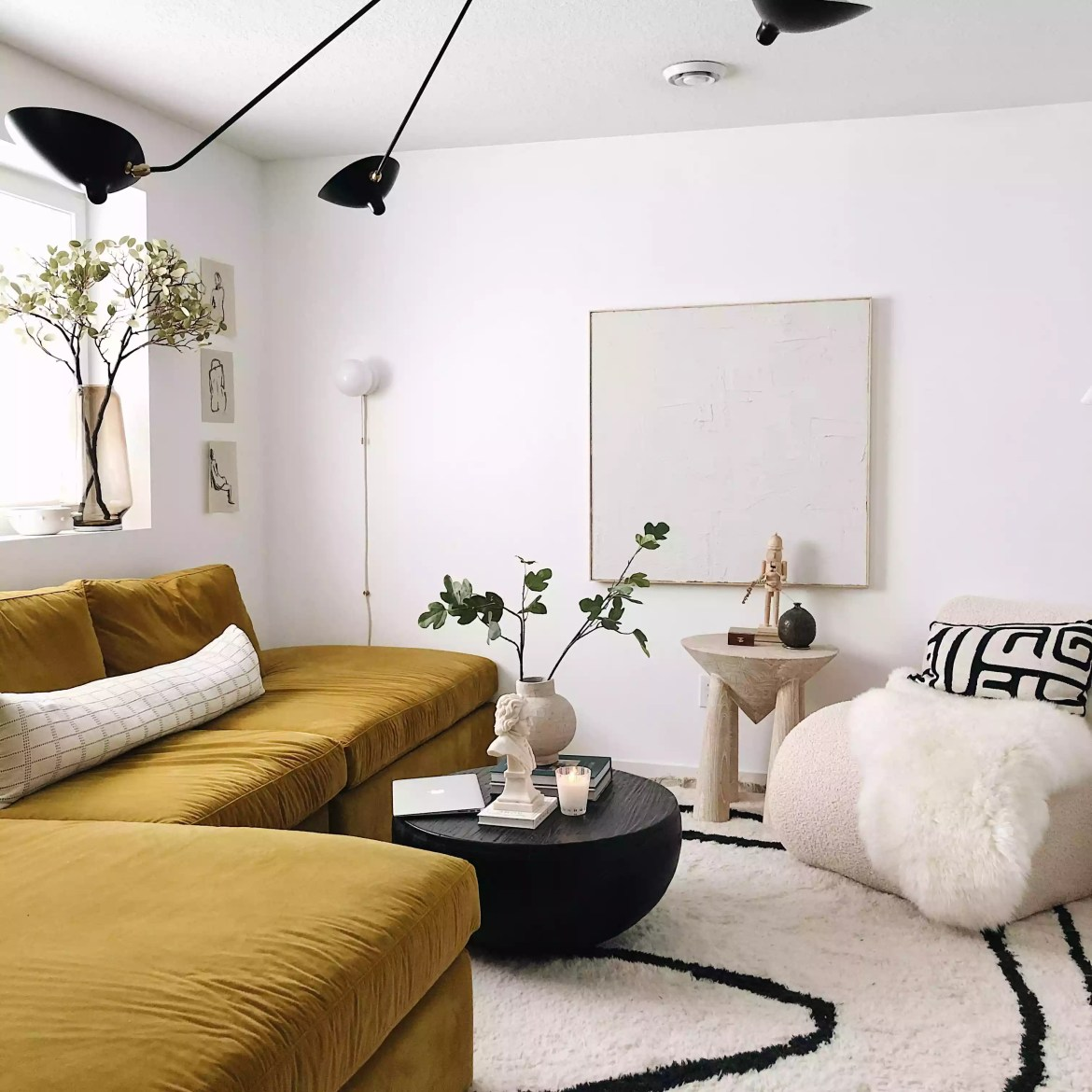 Cozy space with yellow velvet couch and modern light fixture.