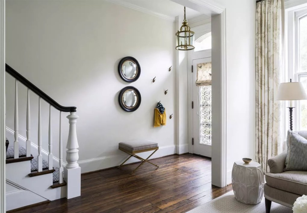 Entryway space with two mirrors and small bench.