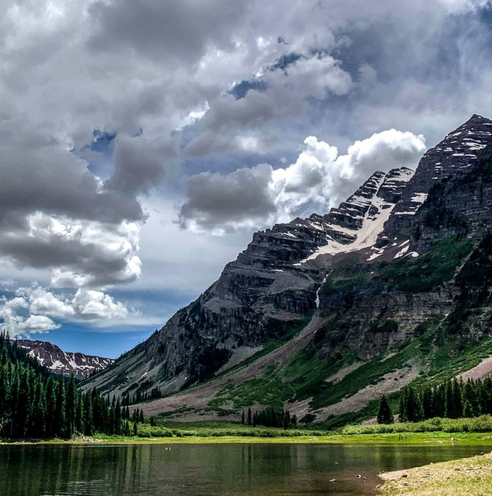 mountain and lake with clouds and trees and grass and rocks and sky