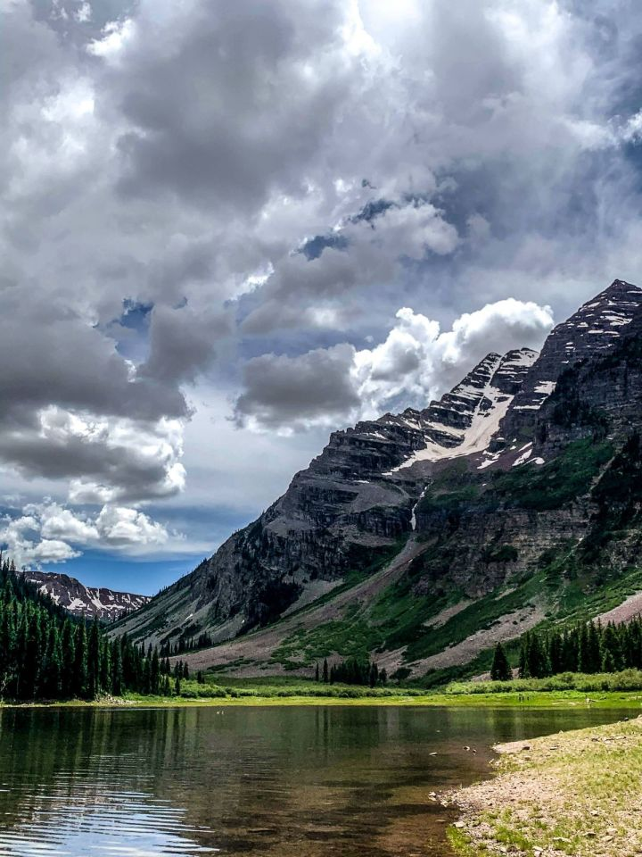 mountain and snow and lake and trees and grass and rocks and clouds and sky
