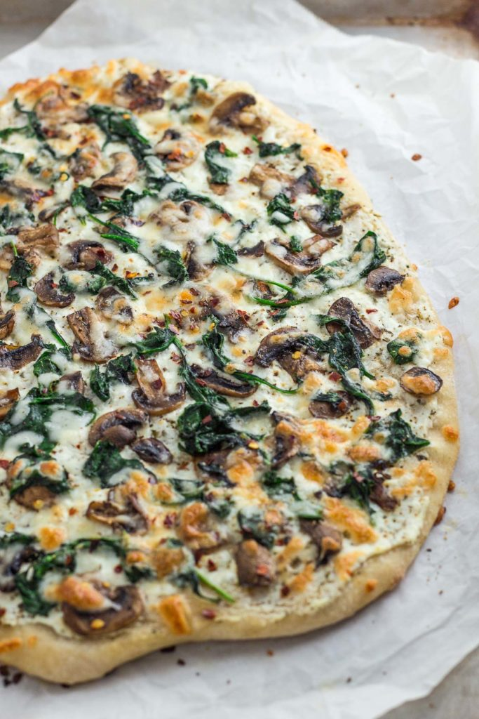 Whole mushroom spinach white pizza on the baking sheet after baking in the oven
